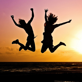 people jumping of happiness on a sunset